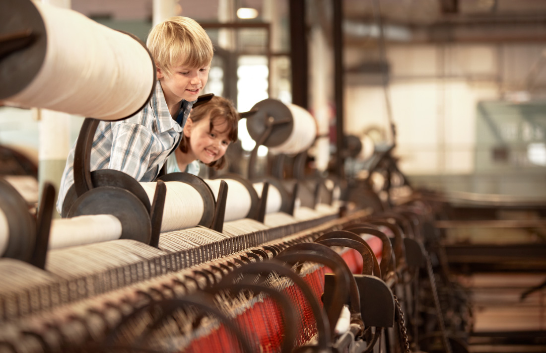 Two children looking at looms for page on Helmshore Mills Textile Museum on the Visit Rossendale website